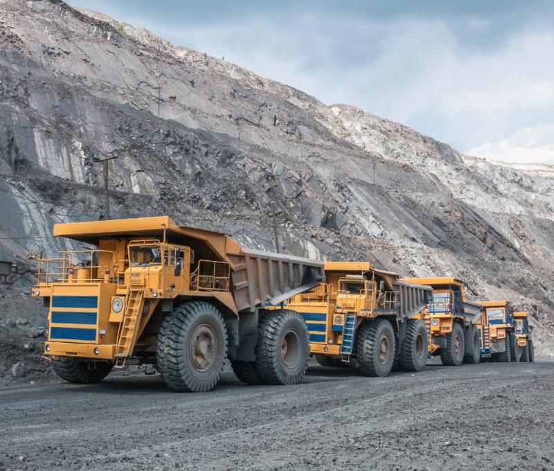 Fleet of yellow trucks on a mine site
